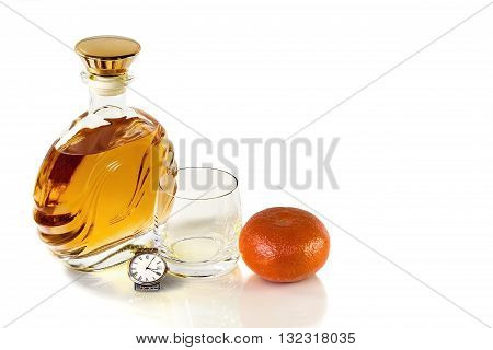 Bottle of whiskey and an empty tumbler with a Mandarin on a white background