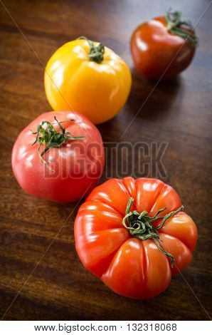 Colorful juicy heirloom or heritage tomatoes on wooden table