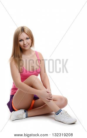 young blonde woman wearing sports clothes sitting on a white floor isolated white