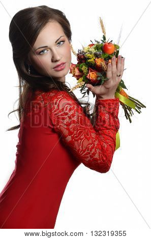 Beautiful young girl in a red dress with a bouquet of flowers
