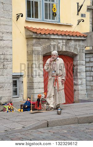 TALLINN, ESTONIA - JUNE 07, 2014: The actor-puppeteer in medieval dress shows a representation of the streets of the old town