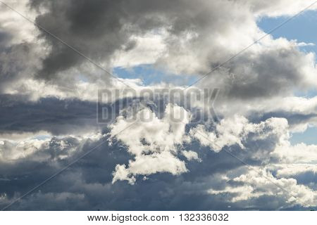 Cumulus Clouds And Grey Storm Clouds Gathering On Blue Sky