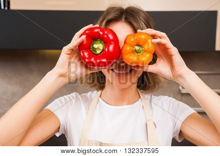 Funny picture of a woman holding big papricas in front of her face