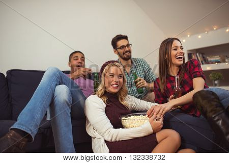 Friends enjoying watching movies together at home.