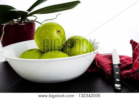 Green apples in white dish with knife on side