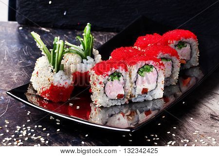 beautiful sushi roll with crab, cucumber and tobiko caviar in a restaurant on a black graphite board, sesame