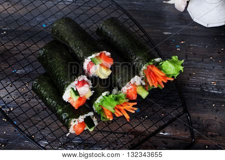 roll sushi black background different tastes, crab carrots lettuce tofu, salmon, still life home stylish, wooden worktops table