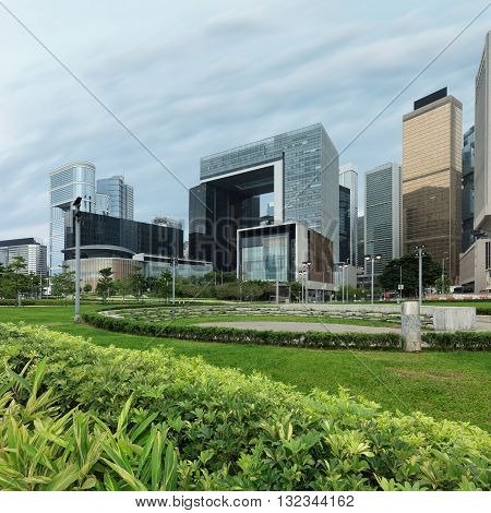 Hong Kong island central quay with greenary on foreground. Modern city architecture