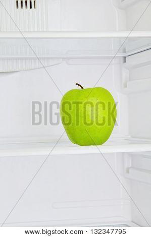 Lifestile concept.Big green apple in domestic refrigerator taken closeup.Toned image.