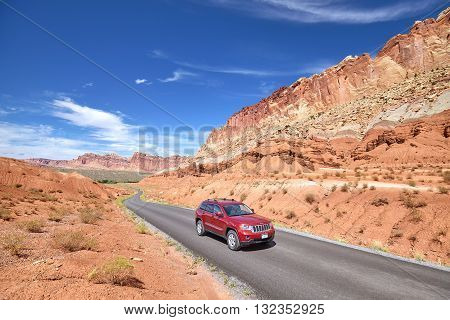Capitol Reef National Park Utah USA - September 3 2015: Picture of a SUV on winding road. Man driving Jeep Cherokee through the park.