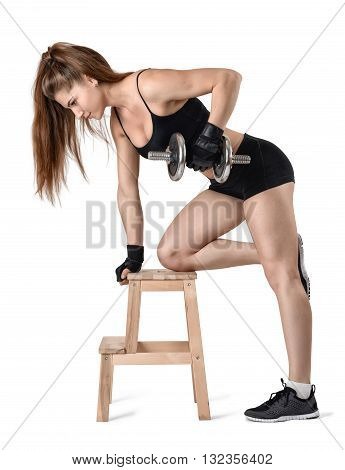 Cutout portrait of muscular young woman lifting a dumbbell for training her biceps leaning on the chair. Power training. Power of body. Sportswear for training. Fitness and sport. Healthy lifestyle.