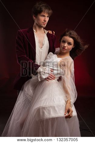 pretty young lady in old time and man in green in medieval dress over red background
