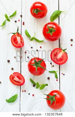 Vegetables background. Tomatoes, basil and garlic on white wooden table. Food background with copy space.