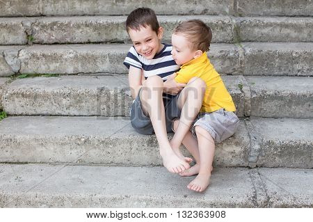cheerful brothers playfully fighting and tickle each other. Two laughing boys hugging and tickling each other on the stairs