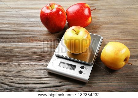 Apples with digital kitchen scales on wooden background