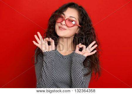 young woman beautiful portrait show okay sign, posing on red background, long curly hair, sunglasses in heart shape, glamour concept
