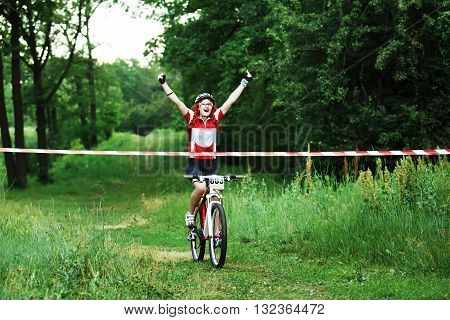 Winner of mtb race. Victory moment. Young female cyclist in protective helmet crossing the finish line breaking the tape. Victory triumph in sportive competition, wins the cycling race. Bicycle sport.