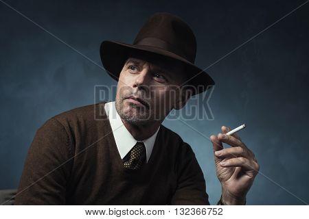 Portrait of vintage 1940 businessman smoking cigarette.