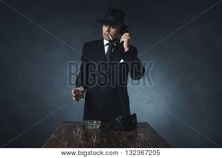 Retro 1940 Businessman On The Phone With Cigarette In Mouth. Standing Behind Wooden Table.
