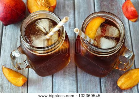 Two Mason Jar Glasses Of Homemade Peach Iced Tea On A Rustic Wood Background, Downward View