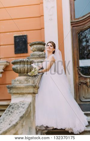 Beautiful bride in elegant white dress with long tail posing stairs romantic vintage building near baluster.