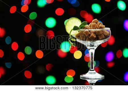 Margarita glass with brown lump sugar on dark bokeh background