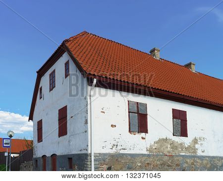 White Painted Old House With Red Roof In Ventspils