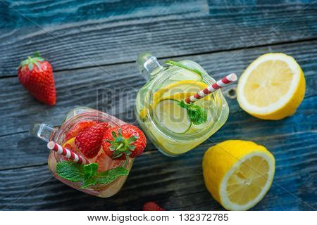 Jugs With Lemon, Lime And Strawberry Infused Water On A Rustic Wooden Surface