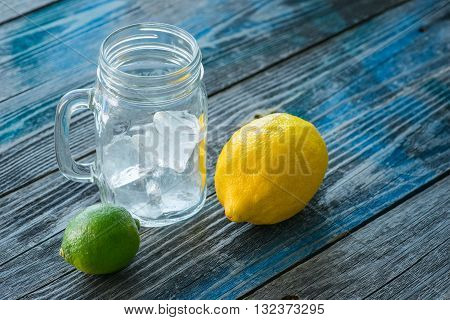 Glass jar with melted ice cubes and citrus fruits on a rustic wooden table