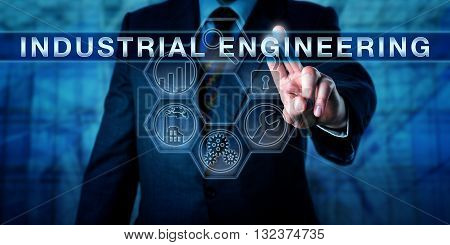 Manager touching INDUSTRIAL ENGINEERING on a visual interactive control screen. Production and manufacturing metaphor. Business and industrial concept for managing process and systems optimization.