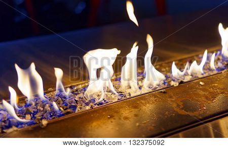 Blue tongue of fire flames burning in the fireplace in the dark premises late in the evening
