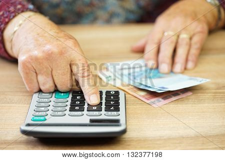 Older woman is using calculator to calculate all expenses