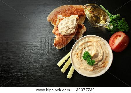 Ceramic bowl of tasty hummus with parsley on table