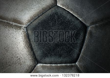Macro photo of an old black and white soccer ball with pentagons and hexagons in leather