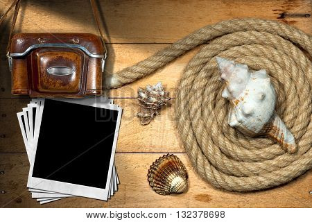 Old and vintage camera with leather case and a group of empty instant photos on a wooden background with nautical rope and three seashells