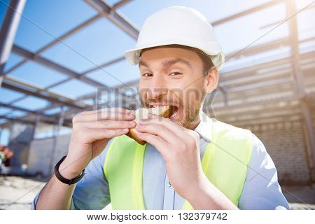 Tasty sandwich.  Smiling and positive builder having lunch and eating tasty sandwiches while being on construction and looking at a camera