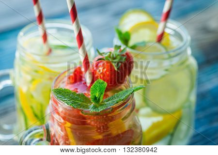 Jugs With Lemon, Lime, Strawberry And Cucumber Infused Water On A Rustic Wooden Surface