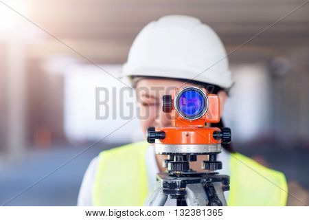 Level usage. Concentrated and busy young woman using a geodetic level standing in a new building