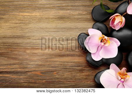 Spa stones and orchid flowers on wooden background