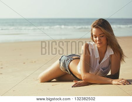 young pretty blond woman at seacoast walking relaxing, fashion lady at sunset, lifestyle people concept