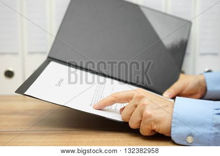 businessman is reading contract in office at the desk