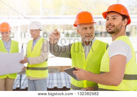 Instructions for colleagues. Cheerful and positive pair of engineers standing together and talking about directions with another pair of engineers in a background