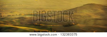 Wavy fields in Tuscany at sunset, Italy. Natural outdoor seasonal spring background. Panoramic view.