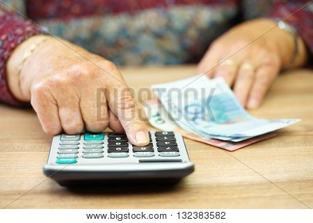 pensioner is calculating how to split money for costs
