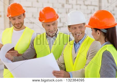 Pleasant working atmosphere. Smiling and cheerful positive group of engineers standing together, looking at a plan and discussing some details while being at construction works