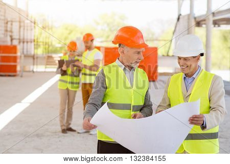 Cheerful colleagues. Delighted and positive pair of engineers standing together, looking at a building plan with another content pair of workers in a background