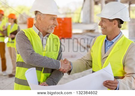 Coming to terms. Happy and positive pair of businessmen standing and shaking hands while holding a construction plan with a pair of architects in a background