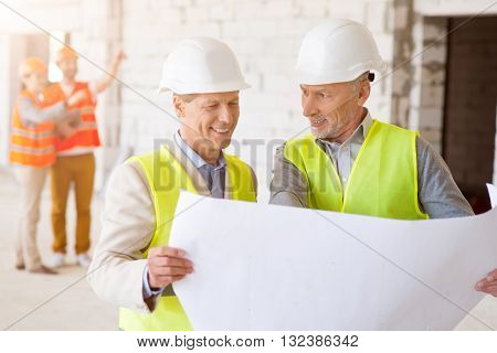 Rule and control. Positive and busy pair of businessmen controlling building process while holding construction plans with a pair of architects standing in a background
