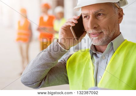 Important call. Pleasant and attentive architect making a phone call with his colleagues standing in a background