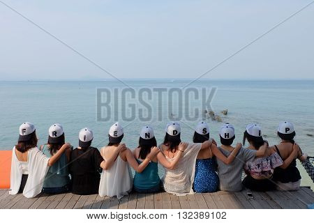 women friend group sit make arm hug hold around their friend's shoulder on wooden pier. They wear same design caps with FRIENDSHIP alphabets on each one. looking at empty blue sea sky.